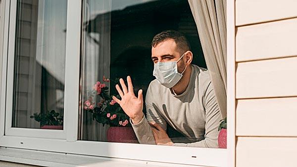 Mann winkt aus Fenster